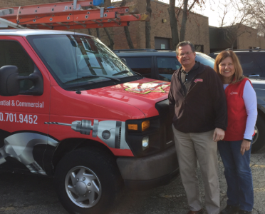 Wayne Owczarzak and his wife in front of a Mr. Handyman truck